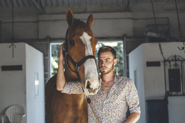 Portrait of young man leading horse in stable on ranch