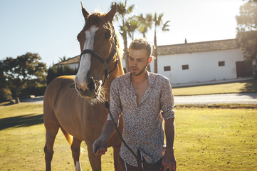Young man leading brown horse in field with back light and lens flare