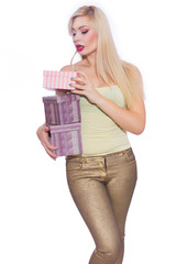 Studio photo of a beautiful young blond woman with long hair dressed in a summer light yellow jersey and golden jeans. The girl is holding boxes with gifts. A model poses against a white background.
