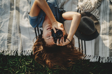 Shot of young happy smiling girl with long hair lying on grass taking a photo on vintage film camera, beautiful smiling hipster girl chilling in the park, lifestyle relax and holidays