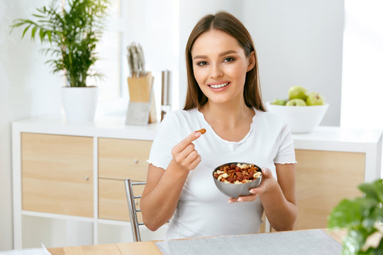 Smiling Woman Eating Nuts In Kitchen