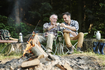 Fishermen drinking coffee beside bonfire