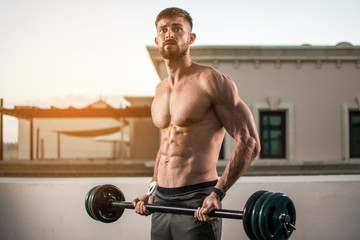 Muscular bearded man doing exercises with barbells outdoors.
