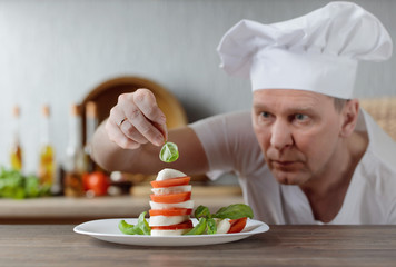 Chef prepares a snack with mozzarella , tomatoes and basil .