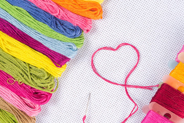 Colored thread for embroidery on white canvas. The concept of love for a hobby.