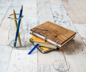 Notebooks and pencils on vintage wooden background