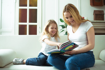 Beautiful smiling blond mother and daughter are sitting on the couch in an embrace. Mom is reading a story to her daughter or a fairy tale from a book.