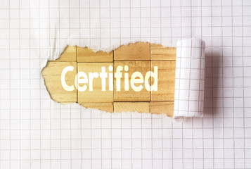 Paper tear on cube wood background with certified text