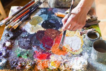 Close up of woman artist painting oils in his studio, Watercolor palette