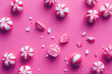 Pink and white striped sweets on pink background.