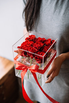 Woman holding transparent flower box filled with red roses with a red polka dotted bow on it
