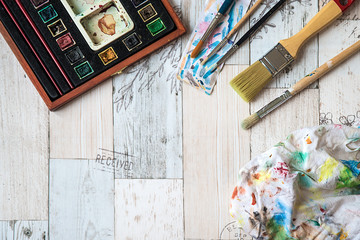 Watercolors and paintbrushes on wooden background