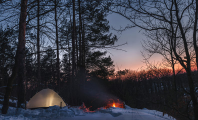 Campfire burns in the snow in the forest hill, on a background of snow covered trees and mountains campfire burning in cold winter. night fire and tent. Hiking Tourism. Flames, background