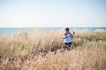 happy free little boy running across field of dried grass on sea background in summer