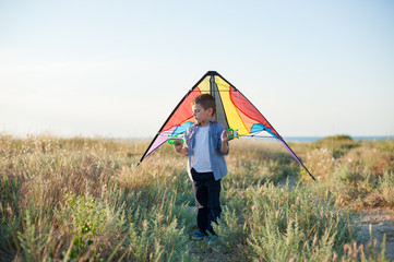 handsome dreamy little boy with closed eyes holds colorful kite behind dreaming