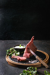 Grilled sliced rack of lamb with yogurt mint sauce served with green salad young beetroot leaves, knife and pink salt on round wooden slate board over dark black table background. Copy space
