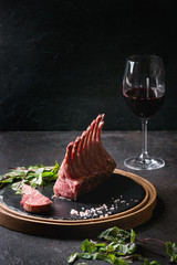 Grilled sliced rack of lamb with yogurt mint sauce served with green salad young beetroot leaves, glass of red wine, pink salt on round wooden slate board over dark black table background. Copy space