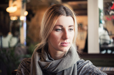 Close-up portrait young romantic beautiful blonde woman with long hair, wearing in grey scarf, sitting in modern city coffee shop