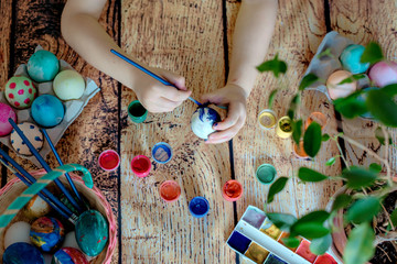 hands paint eggs with a brush