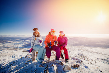 A group of gay girlfriend girls sit on the top of the mountain and drink tea and coffee in the winter. Concept holiday company