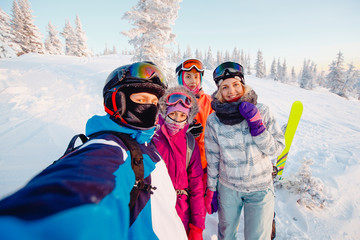 Team of friends makes a selfie photo of herself with snowboards and skis. action camera.