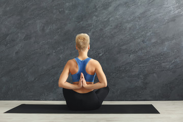 Young woman in yoga class, Reverse Prayer Pose