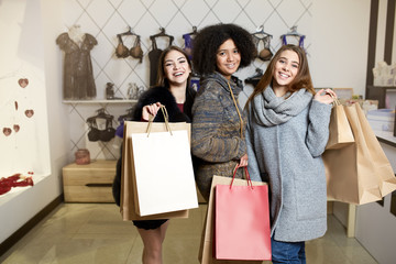 Women of diverse ethnicity with shopping bags posing in lingerie store. Portrait of three pretty multiracial girls walking in underwear shop on sale. Copyspace on large paper craft bags.