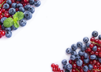 Top view. Red and blue berries. Ripe blueberries and red currants on white. Berries at border of image with copy space for text.