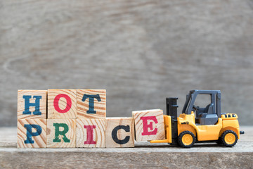 Toy forklift hold letter block E to complete word hot price on wood background