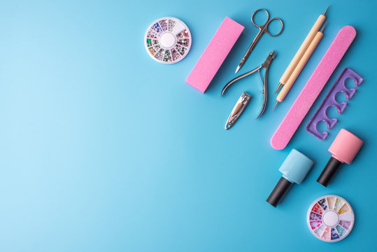 A set of cosmetic tools for manicure and pedicure on a blue background. Gel polishes, nail files and clippers, top view