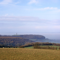 View towards the Tynedale Monument on the edge of the Cotswold Hills escarpment near Wotton Under Edge, Gloucesteshire, UK. The Severn Vale beyond is filled with low lying mist.