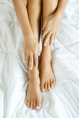 Female feet and hands on soft bed linen