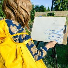 Beginning artist draws on an easel from nature in summer