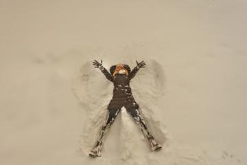 girl lies snow shows  wings angel winter