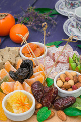 Set of eastern desserts. Marmalade, kivi, prunes, rahat lokum, nuts, mandarin, persimmon, dried apricots, pistachios, dates, raisins in a colorful blue. Wooden rustic background. Top view