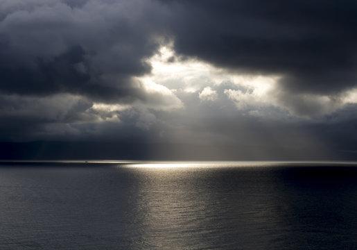 Sun Breaks Through Dark Clouds Over Ocean