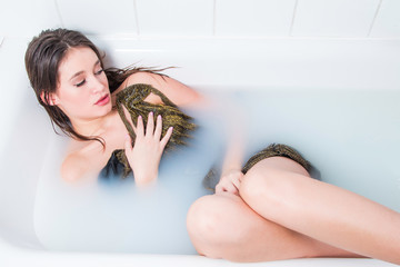 Beautiful young model girl in golden dress in bath, glamour concept