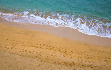 Beach with Footprints and Bright Clear Ocean