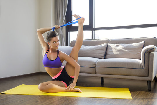 Woman during home workout with а rubber resistance band