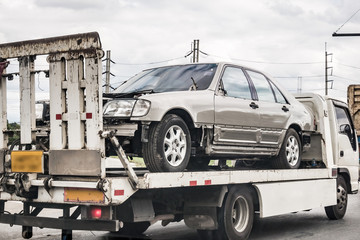 Broken car on tow truck after traffic accident, on the road service