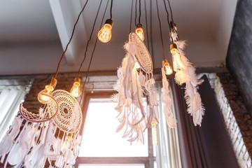 Decorative dream catcher in home interior with edison lamps