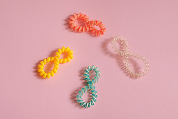 Colorful hair bands in the form of number 8 on pink background. Place for text, design, pattern.