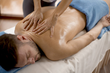 Young man having massage in the spa