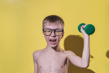 Small boy in glasses holding dumbbell in hand. Child's face feeling very heavy. Funny sport concept.