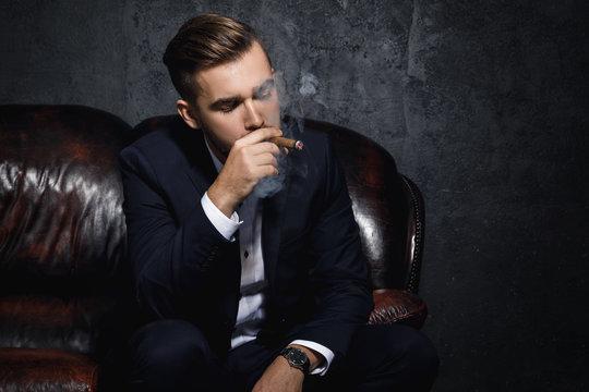 Handsome rich man is smoking cigar