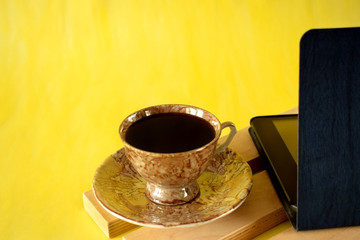 Cup of coffee and tablet pc on yellow background. Business workplace. Copy space