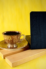Cup of coffee and tablet pc on yellow background. Business workplace