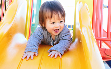 Mixed race toddler boy playing on a slide at a playground