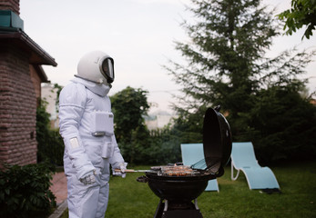 Man in space suit grilling meat