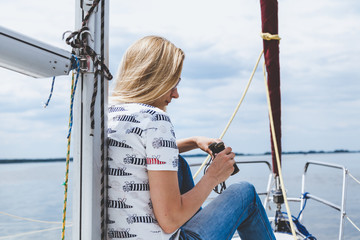 slender blonde in jeans sits on nose of white yacht